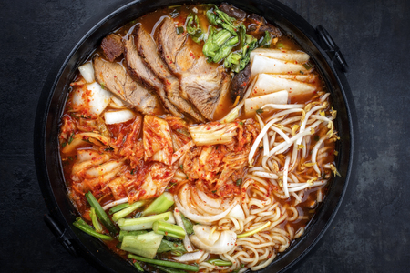 Traditional Korean kimchi jjigae with grilled pork belly and ramen as top view in a pot Фото со стока