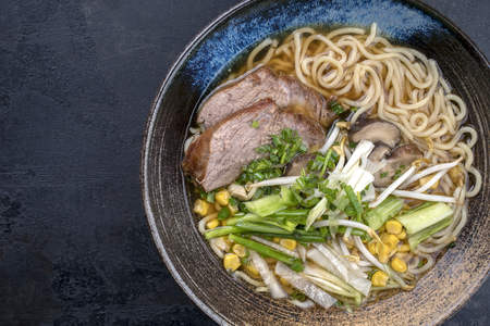 Traditional Japanese shoyu ramen with chashu as top view in a bowl with copy space left