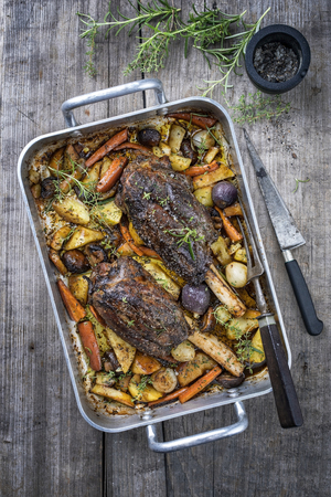 Venison knuckle with fried potatoes and vegetable as top view in a casserole