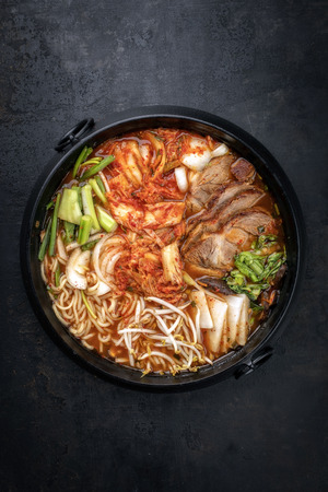 Traditional Korean kimchi jjigae with grilled pork belly and ramen as top view in a pot Imagens