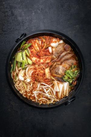 Traditionelles koreanisches Kimchi Jjigae mit gegrilltem Schweinebauch und Ramen als Draufsicht in einem Topf