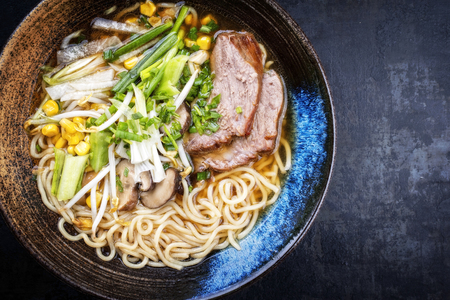 Traditional Japanese shoyu ramen with chashu as top view in a bowl with copy space right