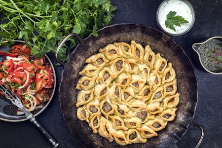 鋳鉄鍋のトップビューとしてミンチミートとパプリカサラダと伝統的なアルメニアのマンティ 写真素材