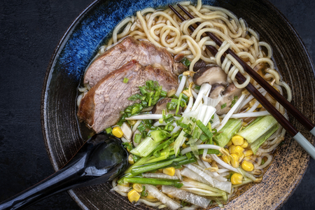 Traditional Japanese shoyu ramen with chashu as top view in a bowl with chopsticks