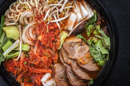 Traditional Korean kimchi jjigae with grilled pork belly and ramen as top view in a pot Stockfoto