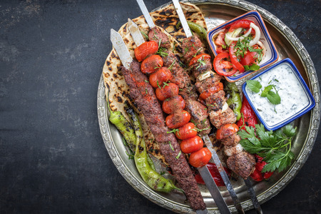 Traditional oriental Adana kebap and shashlik skewer with tomato and flatbread as top view on a plate with copy space left Banco de Imagens