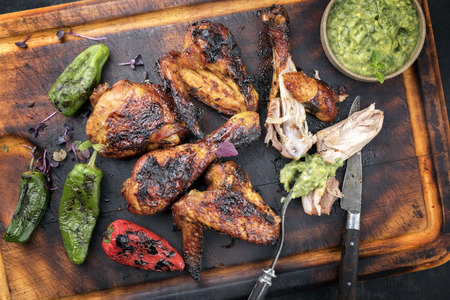 Traditional Caribbean barbecue chicken wings and drumsticks with chimichurri sauce, jalapeno and poblano chili as top view on an old wooden cutting board