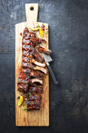Barbecue spare ribs St Louis cut with hot honey chili marinade and chili as top view in a wooden cutting board with copy space