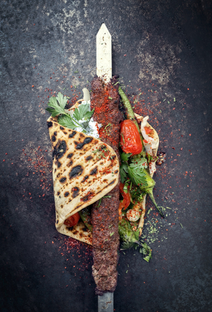 Traditional Adana kebap on a skewer with tomato and yogurt as top view on a flatbread Stock Photo