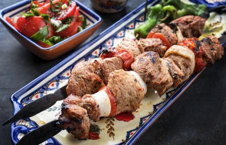 Traditional Greek souvlaki barbecue skewer  tomato onion salad and paprika as closeup on a plate Stock Photo