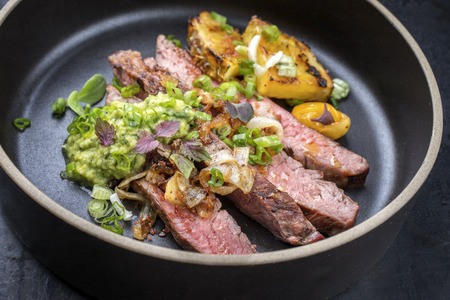 Modern Barbecue dry aged wagyu flank steak with pineapples and chimichurri sauce as closeup on a plate