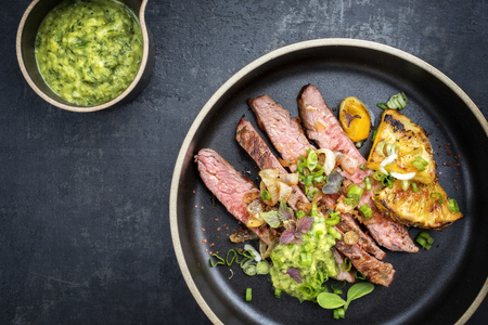 Modern Barbecue dry aged wagyu flank steak with pineapples and chimichurri sauce as top view on a plate Stock Photo
