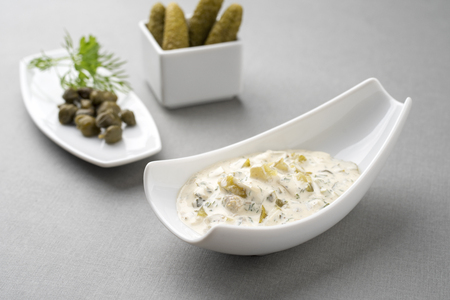 Modern design German remoulade with gherkin and cappers offered in a bowl on a gray board Stock Photo
