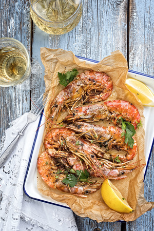 Traditional fried black tiger prawn with lemon and white wine as top view in a white casserole on a wooden blue board Stock Photo