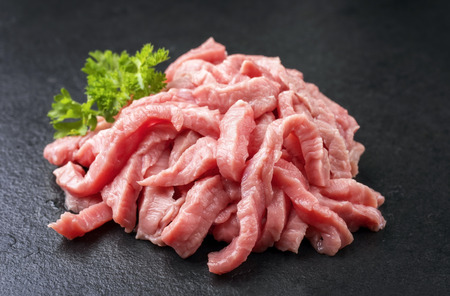 Raw veal strips for traditional Swiss zürcher geschnetzeltes with herbs as closeup on a black slate slab