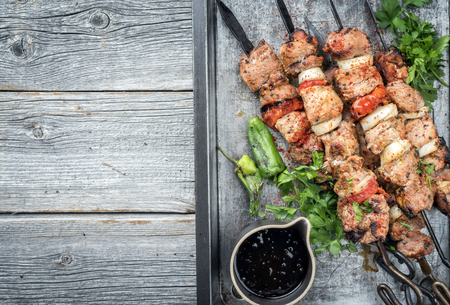 Traditional Greek souvlaki barbecue skewer with tomato, onion and paprika as closeup on a metal griddle with copy space left Reklamní fotografie