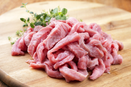 Raw veal strips for traditional Swiss zürcher geschnetzeltes with herbs as closeup on a wooden cutting board