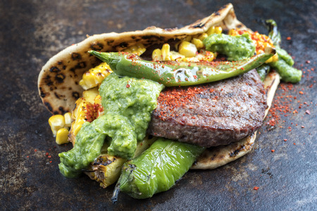 Barbecue wagyu hash burger with flatbread, pineapple and chimichurri sauce as top view on an old metal sheet