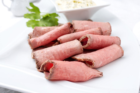 Traditional lunch meat with sliced cold cuts roast beef and remoulade as closeup on a white plate Stockfoto