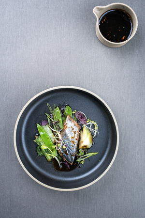 Modern style Japanese bonito tuna fish filet with vegetable glazed in teriyaki sauce as top view on a plate with copy space Stock Photo