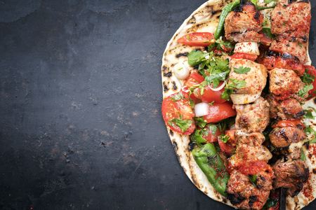 Traditional Greek souvlaki barbecue skewer with tomato, onion and paprika as closeup on a metal griddle with copy space left Banco de Imagens