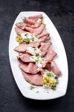 Traditional lunch meat with sliced cold cuts roast beef and remoulade as closeup on a white plate Stock Photo