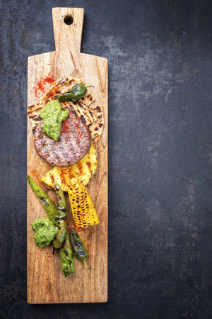 Barbecue wagyu hash burger with flatbread, pineapple and chimichurri sauce as top view on a cutting board with copy space right