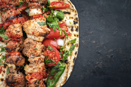 Traditional Greek souvlaki barbecue skewer with tomato, onion and paprika as closeup on a metal griddle with copy space right Stock Photo