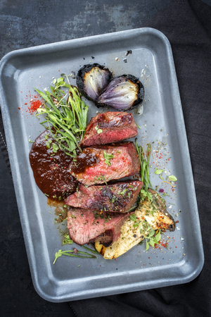 Modern Style Italian barbecue dry aged sliced chateaubriand with mushroom and onion as top view in a skillet Stock Photo