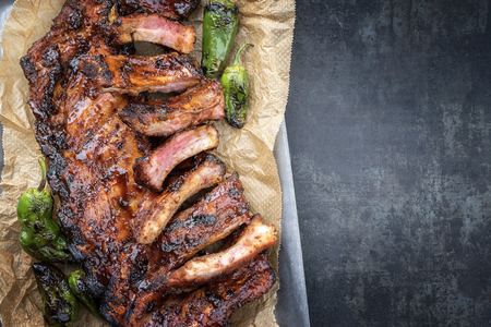 Barbecue spare ribs St Louis cut with hot honey chili marinade and jalapeno as top view in a rustic skillet and backing paper with copy space right