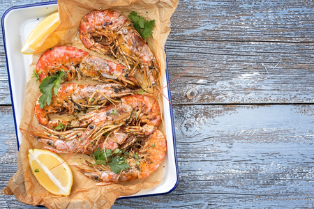 Traditional fried black tiger prawn with lemon as top view in a white casserole on a wooden blue board