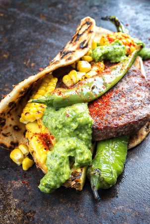 Barbecue wagyu hash burger with flatbread, pineapple and chimichurri sauce as closeup on an old metal sheet Stock Photo