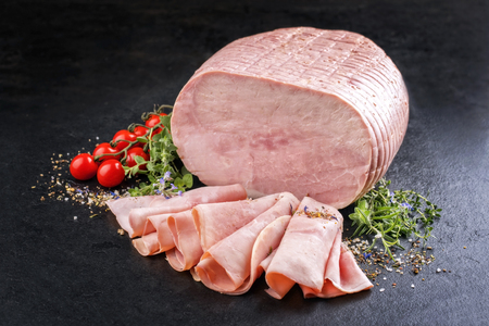 Traditional German boiled ham as piece and sliced decorated with tomatoes and herbs as top view on black slate slab with copy space Stock Photo