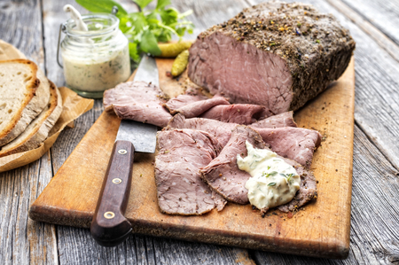 Traditional lunch meat with sliced cold cuts roast beef, remoulade and farmhouse bread as closeup on a cutting board Stock Photo