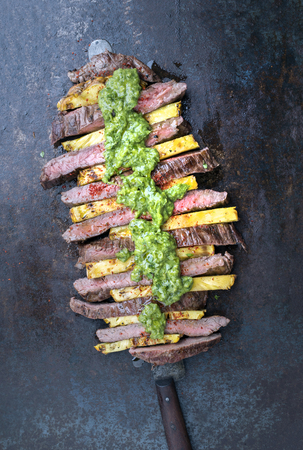 Traditional Barbecue dry aged wagyu flank steak with pineapples and chimichurri sauce as top view on a knife on an old metal sheet with copy space Stock Photo