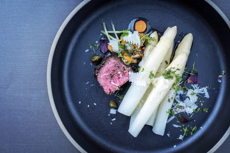 Modern Italian barbecue dry aged tagliata di manzo with white asparagus and parmesan as top view on a plate with copy space left Stock Photo