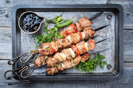 Traditional Greek souvlaki barbecue skewer with tomato, onion and paprika as closeup on a metal griddle Imagens
