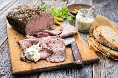 Traditional lunch meat with sliced cold cuts roast beef, remoulade and farmhouse bread as closeup on a cutting board Stok Fotoğraf