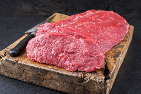 Raw roast beef offered as closeup on an old rustic wooden cutting board Banque d'images