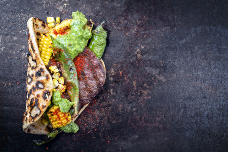 Barbecue wagyu hash burger with flatbread, corn and chimichurri sauce as top view on a old metal sheet with copy space right