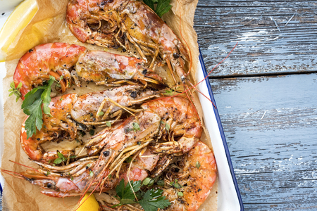 Traditional fried black tiger prawn with lemon and white wine as top view in a white casserole on a wooden blue board with copy space right