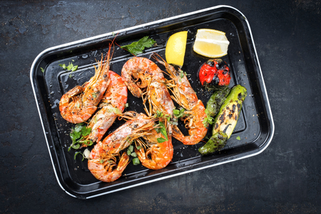 Traditional fried black tiger prawn with vegetable and lemon as top view on a black skillet
