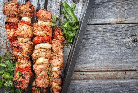 Traditional Greek souvlaki barbecue skewer with tomato, onion and paprika as closeup on a metal griddle with copy space right Imagens