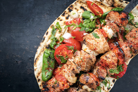 Traditional Greek souvlaki barbecue skewer with tomato, onion and paprika as closeup on a metal griddle with copy space left Imagens