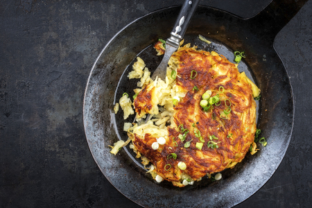 Top view of traditional Swiss rosti with leek in a frying pan with copy space