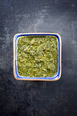 Top view traditional Columbian chimichurri sauce aji criollo with chili, coriander and garlic  in a bowl with copy space Stock Photo