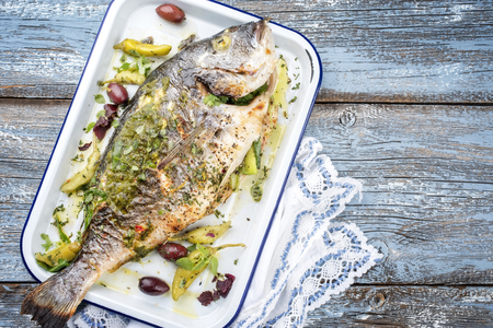 Fresh Greek barbecue gilthead seabream with peperoni and Kalamata olives as top view in a white skillet Stock Photo