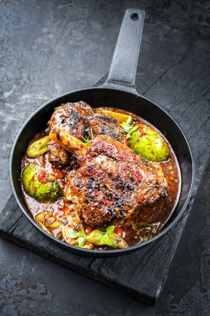 Traditional barbecue leg of lamb with lemon and tomatoes as closeup in a cast-iron skillet