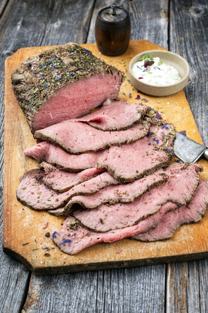 Traditional lunch meat with sliced cold cuts roast beef and remoulade as closeup on a cutting board