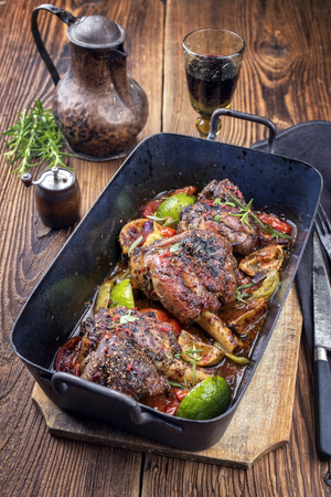 Traditional barbecue leg of lamb with lemon and tomatoes as closeup in an old skillet